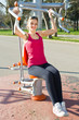 Portrait of cheerful woman in fitness wear exercising with equip