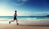 Man running on tropical beach at sunset