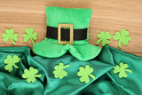 Saint Patrick day hat with clover leaves on wooden background