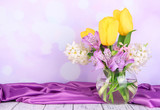 Flowers in vase on table on bright background