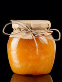 Orange jelly in glass jar isolated on black