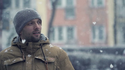 Young man in the city during blizzard, super slow motion