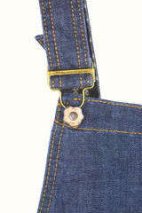 metal button of dungarees close up on white wall