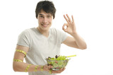 Man measuring biceps with centimeter while eating organic salad