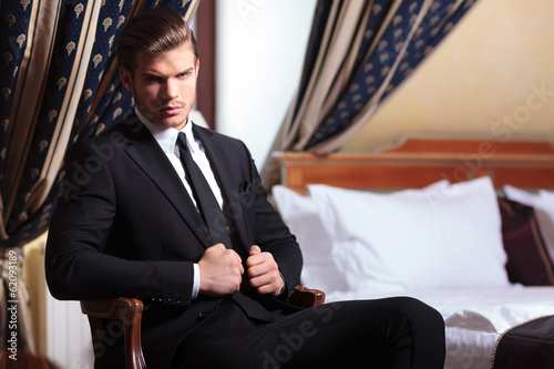 seated young business man looks at you