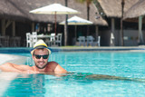 man wearing hat and sunglasses relaxing at the pool