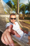 man in a hammock in a resort pointing his finger