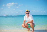 casual man  standing crouched on a tropical beach