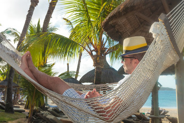 happy young man resting in a hammock on the beach