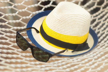 straw hat and sunglasses on a hammock