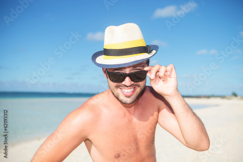 man on the beach taking off his glasses and smiles