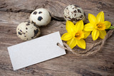Quail eggs and  daffodils with a  tag