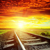 sunset with red clouds and railroad to horizon