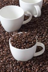 Drei Kaffeetassen, eine mit Kaffeebohnen gefüllt