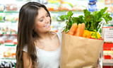 Young woman holding a shopping bag full of vegetables