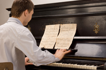 Young pianist sitting practicing at the piano