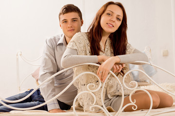 Attractive friendly young couple relaxing on a bed