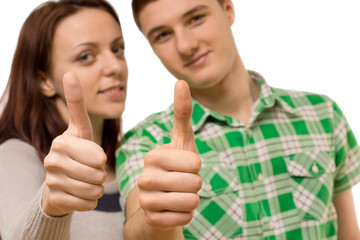 Attractive young couple giving a thumbs up