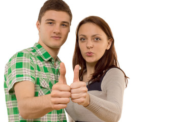 Motivated young couple giving a thumbs up