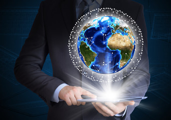 Man in suit holding tablet pc and earth in hand