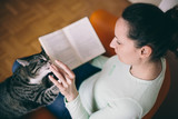 Young woman reading book playing with cat