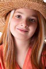 portrait of little red-haired girl with freckles and a straw hat