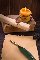 Old paper candle and quill pen