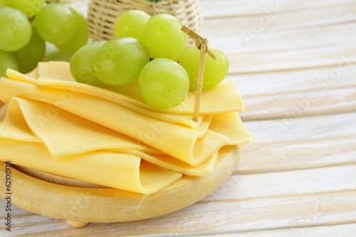 cheese served on a wooden board with green grapes