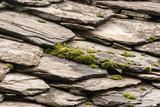 Stone tiles of slate-roof rural house as background