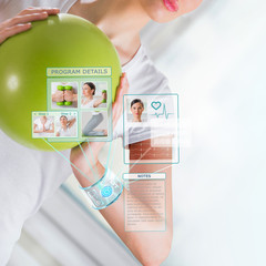 Woman doing exercise with ball wearing smart wearable device wit