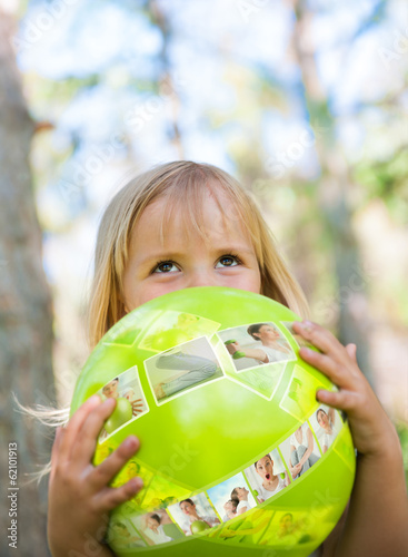 Little girl playing with green ball in the park
