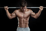 Fototapety Muscular bodybuilder guy doing exercises with dumbbells over bla