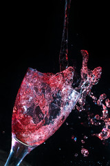 Wine pouring and spilling into a glass frozen in time
