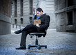 Business Man sitting on Office Chair on Street in stress - 62104153