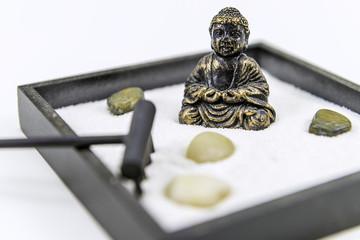 Zen garden with rocks, rake and a Buddha