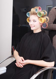 woman in salon, blond girl hair curlers rollers by hairdresser