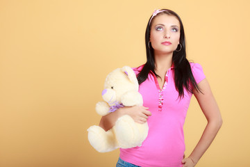 Childish young woman infantile girl hugging teddy bear toy