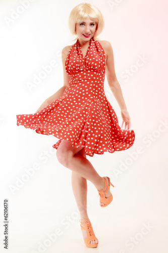 Pinup girl in blond wig and retro red dress dancing. Party.
