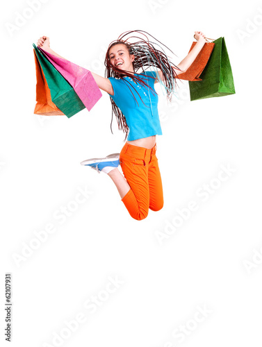 Happy girl jumping with shopping bags, white background