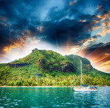 Polynesia. Island and vegetation at sunset with small boat on fo