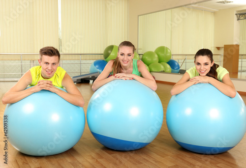 Group of young people training with gymnastic ball in gym