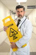 Hispanic Doctor Holding Caution Sign