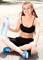 Sport girl sitting with water