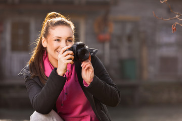 Young woman holding camera and taking photo outside