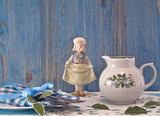 Small jug and antique doll on blue wooden background.