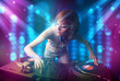 Dj girl mixing music in a club with blue and purple lights