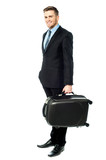Happy young business man holding suitcase