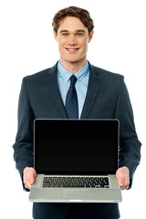 Corporate executive showing laptop to camera