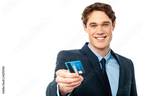 Smiling businessman offering his debit card to you