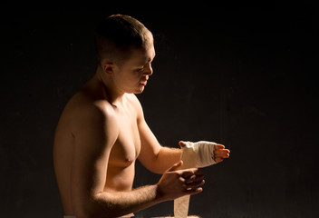 Young boxer psyching himself up in the darkness